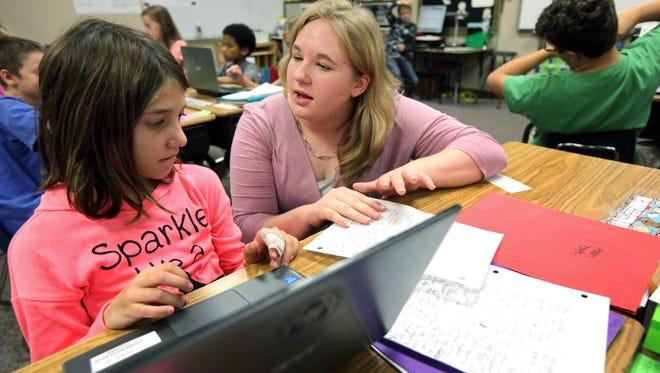 Courtney Rickett, a student teacher at Harvey Dunn Elementary, helps fourth grade student Emily Denevan during writing class on Thursday.