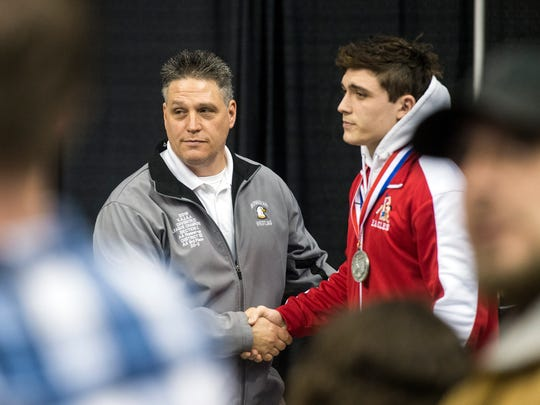 Bermudian Springs assistant coach Dan Dull, left, shakes his son's hand after Chase earned second place at 195 pounds in the PIAA 2A tournament in March 2018.