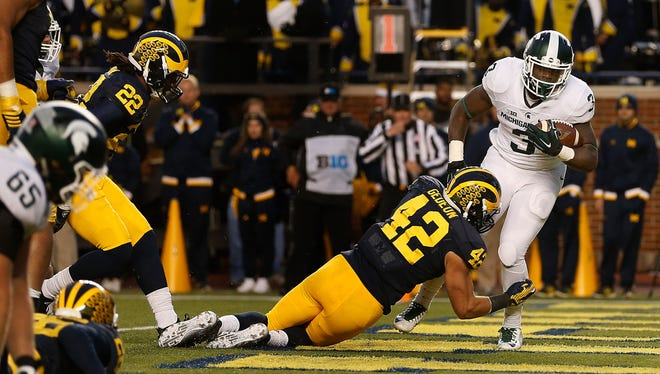 LJ Scott scores while Ben Gedeon makes the tackle during last year's game in Ann Arbor. Both players return for this Saturday's matchup in East Lansing.