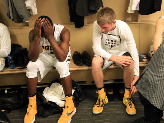 Iowa's Anthony Clemmons, left, sits in the locker room