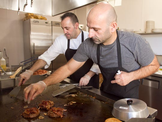 Bill Korkut, left, and brother Niko Korkut, co-owners of Howell Coney Island, prepare food Wednesday, Nov. 8, 2017 on their second day of business.