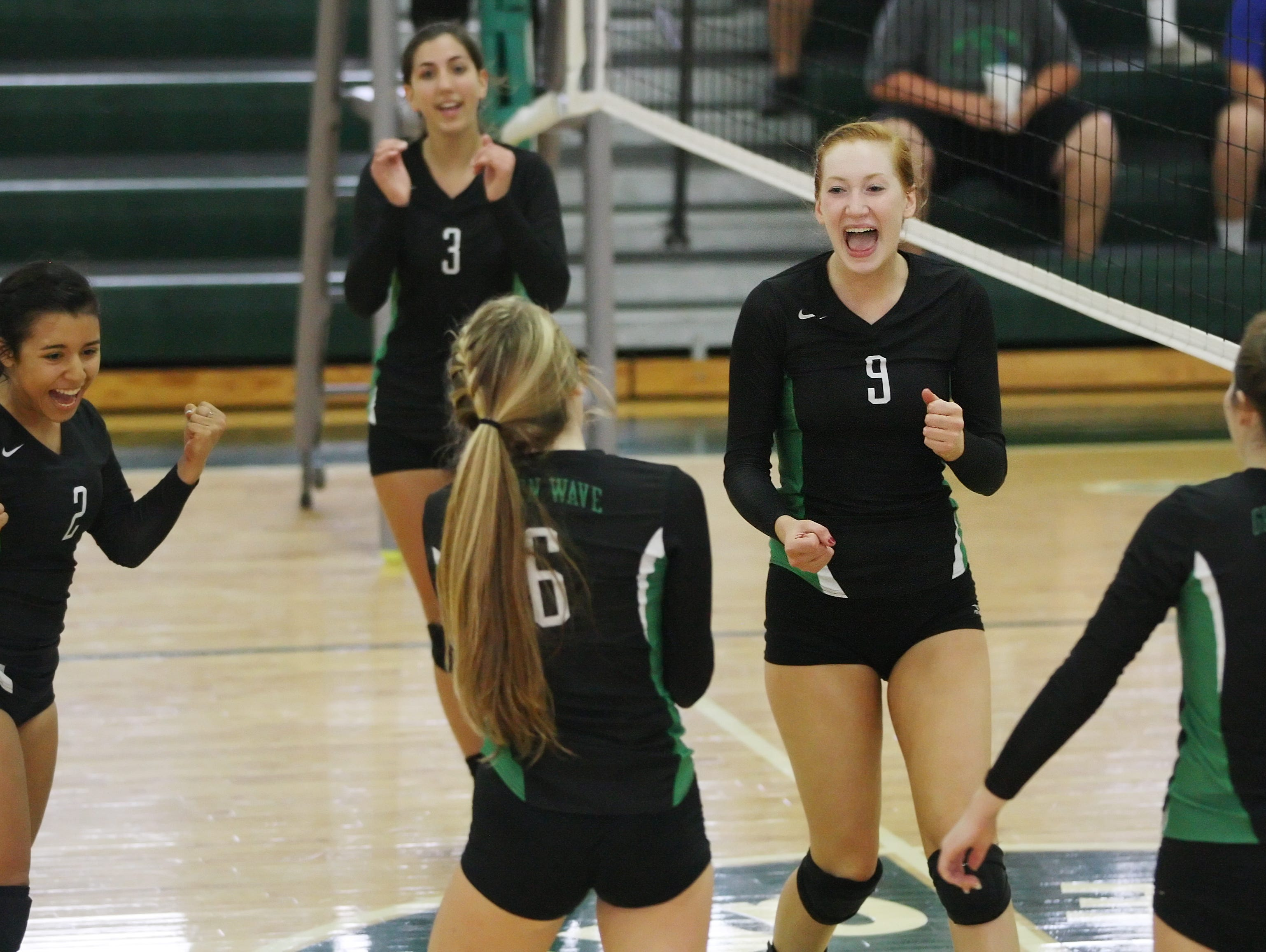 Fort Myers High School's Kaitlin Stewart, second from right, celebrates scoring a point against Barron Collier in the Region 6A-3 semifinal volleyball game Saturday at Fort Myers High School. Fort Myers beat Barron Collier 3-0.