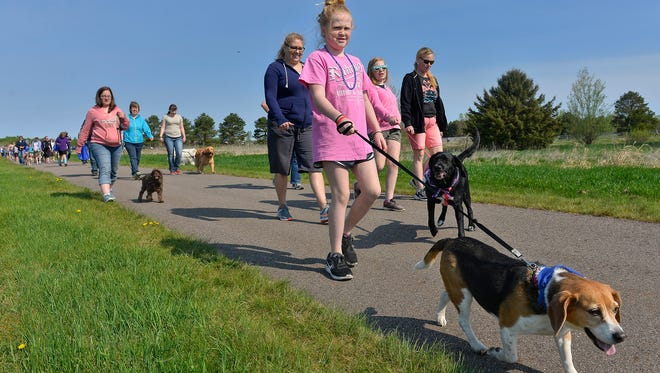 Two-legged participants and their four-legged friends walk in the Bark for Life to raise money for the American Cancer Society on Saturday, May 7, in Sartell's Pinecone Central Park.