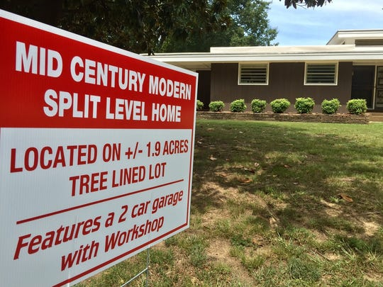 Realtor Judy G. Smith made an extra sign to communicate that the home is bigger than it looks from the street.