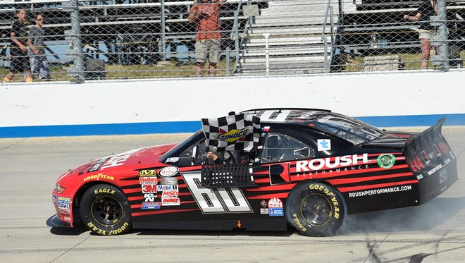 Chris Buescher waves the checkered flag as he drives by the stands and celebrates after he won the NASCAR Xfinity series auto race, Saturday, May 30, 2015, at Dover International Speedway in Dover, Del.