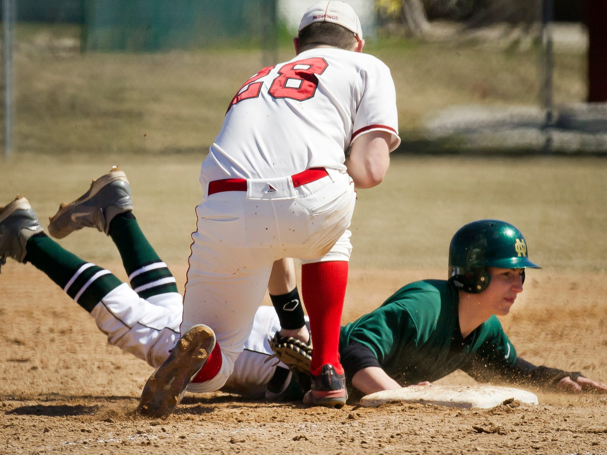 Oshkosh North's Tyler Kujawa (1) makes it to first base in a game against Sheboygan South Saturday.
