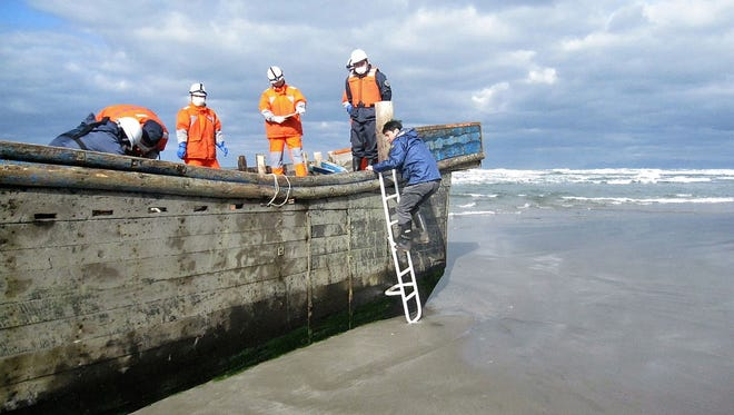 """This handout picture taken on Nov. 27, 2017 by the Oga city municipal office and released via Jiji Press shows coast guard officers inspecting a battered wooden boat where eight bodies were found inside at a beach in Oga, Japan's Akita prefecture. Japanese coastguard officials spotted eight bodies inside a battered wooden boat off northern Akita prefecture but waves had prevented officials from investigating since the boat was first spotted on November 24. Dozens of North Korean fishing vessels wash up on Japan's coast every year. Sometimes the boats' occupants have already died at sea, a phenomenon local media refer to as """"ghost ships"""".   / AFP PHOTO / JIJI PRESS / Handout /  - Japan OUT / RESTRICTED TO EDITORIAL USE - MANDATORY CREDIT """"AFP PHOTO / OGA CITY MUNICIPAL OFFICE / JIJI PRESS"""" - NO MARKETING NO ADVERTISING CAMPAIGNS - DISTRIBUTED AS A SERVICE TO CLIENTS / The erroneous mention[s] appearing in the metadata of this photo by Handout has been modified in AFP systems in the following manner: [adds JAPAN OUT in geographical restriction]. Please immediately remove the erroneous mention[s] from all your online services and delete it (them) from your servers. If you have been authorized by AFP to distribute it (them) to third parties, please ensure that the same actions are carried out by them. Failure to promptly comply with these instructions will entail liability on your part for any continued or post notification usage. Therefore we thank you very much for all your attention and prompt action. We are sorry for the inconvenience this notification may cause and remain at your disposal for any further information you may require.HANDOUT/AFP/Getty Images ORIG FILE ID: AFP_UM8GL"""