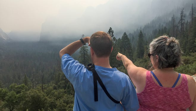 Smoke from the Ferguson Fire blocks landmarks from the view of visitors Brad Lyons, left, and Courtney Richard at Tunnel View in Yosemite National Park.