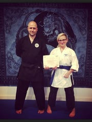"""Sensei Josh Copsin of Blue Dragon Dojang stands beside student Sally Rose Monnes while she holds her certificate for blue belt in the traditional Korean martial art, Oh Do Kwan.  """"My sensei and I started the women's self defense club called Fight Like a Girl. It's for people who feel threatened or unsafe."""""""