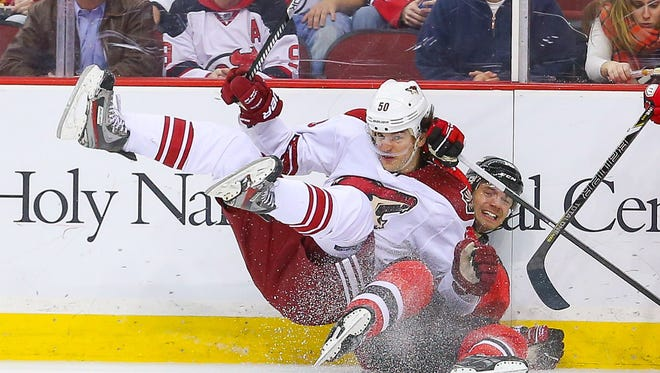 Coyotes center Antoine Vermette (50) and New Jersey Devils center Jacob Josefson (16) collide during the first period at Prudential Center.