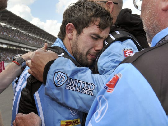 A dejected Carlos Munoz (26) is consoled by a team