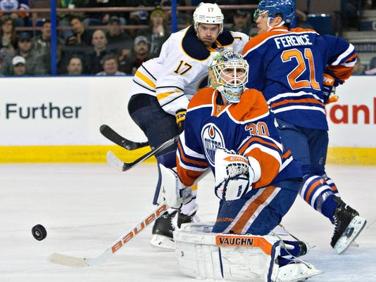 Buffalo Sabres' Torrey Mitchell (17) and Edmonton Oilers' Andrew Ference (21) work next to Edmont goalie Ben Scrivens (30), who turns away the puck during the first period of an NHL hockey game Thursday, Jan. 29, 2015, in Edmonton, Alberta. (AP Photo/The Canadian Press, Jason Franson)