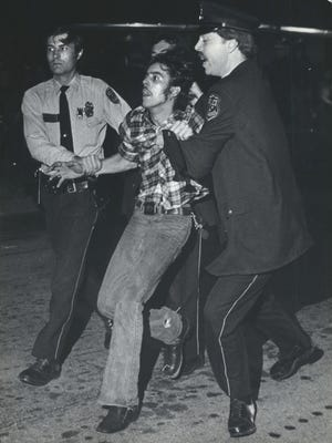 Police pull a concertgoer toward a waiting squad car outside the Milwaukee Arena after a melee broke out at a Black Sabbath-Blue Oyster Cult concert on Oct. 9, 1980. This photo was in the Oct. 10, 1980, Milwaukee Journal.