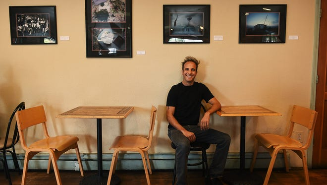 Photographer Shaun Astor poses for a portrait while sitting under some of his work that is being exhibited at Bibo Coffee near UNR in Reno on Oct. 20, 2015.