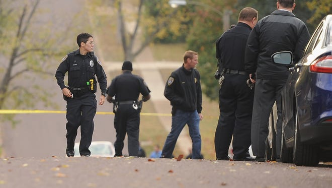 Police officers walk within a crime scene perimeter in Normandy, Mo., on Wednesday, Oct. 28, 2015, while investigating a police-involved shooting.