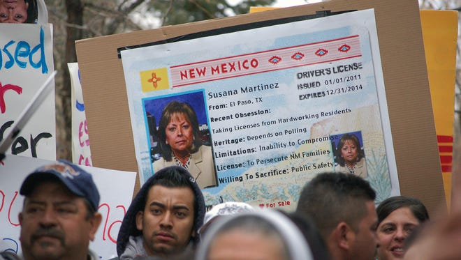 In this Jan. 24, 2012, file photo, immigrant advocates use an image of New Mexico Gov. Susana Martinez on a mock state driver's license during a rally in Santa Fe to protest her proposal to repeal a state law that allows illegal immigrants to obtain driver's licenses.