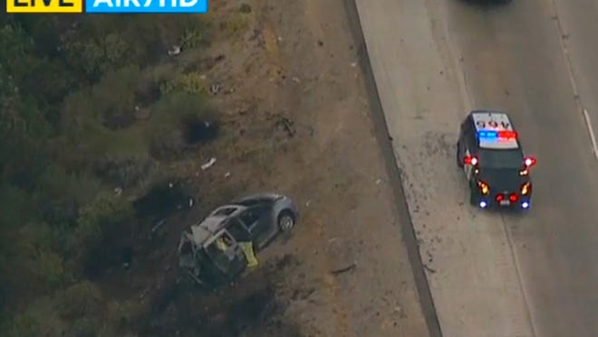 In this image made from video, a minivan burned on the side of Interstate 5, near the community of Gorman in Tejon Pass, about 65 miles north of downtown Los Angeles Tuesday, June 28, 2016. A fiery minivan wreck killed two mothers and their four children on a highway in northern Los Angeles County. The minivan got in a minor collision and stopped on the shoulder. It was still partially in a lane when a semitrailer hit it and it burst into flames with the women and children inside.