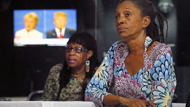 Sharon Ukaha and Cecilia Dennis watch the presidential debate during a party organized by the National Coalition of 100 Black Women on Oct. 19, 2016, in Phoenix.