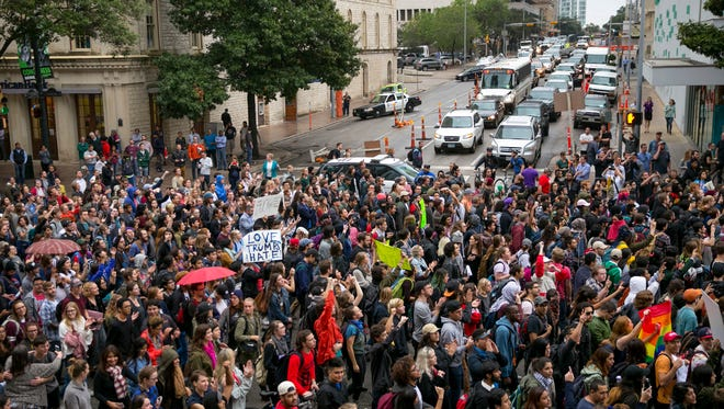 Anti-Trump protesters march along Congress Avenue in Austin, Texas, on Wednesday November 9, 2016. Hundreds of University of Texas students march through downtown Austin in protest of Donald Trump's presidential victory. (Jay Janner/Austin American-Statesman via AP) ORG XMIT: TXAUS109