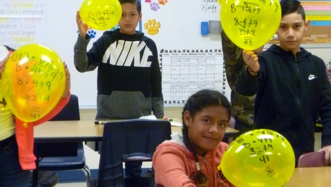 Students in Kim Perea's 5th grade classroom at Bataan Elementary School are having fun figuring out the Order of Operations on balloons. Fifth-grade students must be able to evaluate expressions with parentheses, brackets, or braces. The students receive the foundation for learning which operation (addition, subtraction, division, multiplication), as well as which symbol to perform first in order to evaluate an expression correctly. The students will see this skill on PARCC and 6th grade teachers will build on the Order of Operations next year. Students must be able to add, subtract, multiply, divideand compute square roots and exponents to correctly perform an expression by using the Order of Operations. The acronym PEMDAS (parentheses, exponent, multiplication, division, addition, subtraction) helps the students to remember the correct order to figuring out an expression.