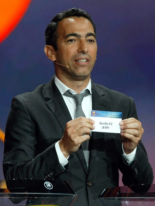 Former French forward Youri Djorkaeff, shows the draw Seville, during the Europa League draw ceremony of the first round of the 2014/2015 Europa League, at the Grimaldi Forum in Monaco, Friday, Aug. 29, 2014. (AP Photo/Claude Paris)