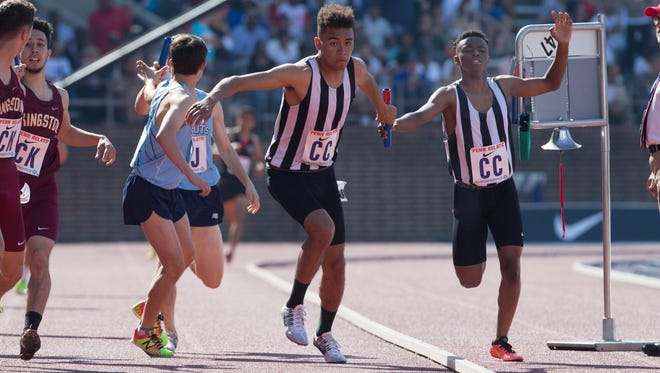 Rey Rivera takes a handoff from Chris Ochieng as he start the anchor leg of his team's High School Boys 4X800 Large School relay on Friday at Penn Relays in Philadelphia, Pa. on April 28, 2017.
