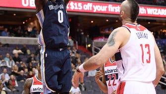 Memphis Grizzlies forward JaMychal Green (0) dunks over Washington Wizards center Marcin Gortat (13), of Poland, during the first half of an NBA basketball game, Wednesday, Dec. 13, 2017, in Washington. (AP Photo/Nick Wass)