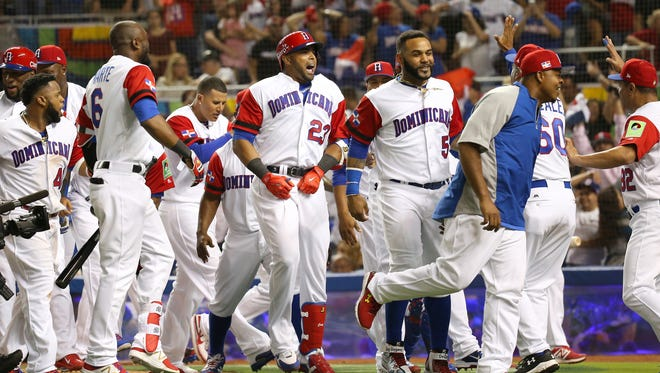 Dominican Republic's Nelson Cruz (23) is congratulated by teammates after hitting a three-run home run against the United States in a World Baseball Classic game at Marlins Park on Saturday, March 11, 2017, in Miami.