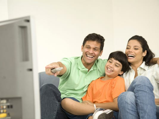 Boy (8-9) with his parents sitting on couch and watching television