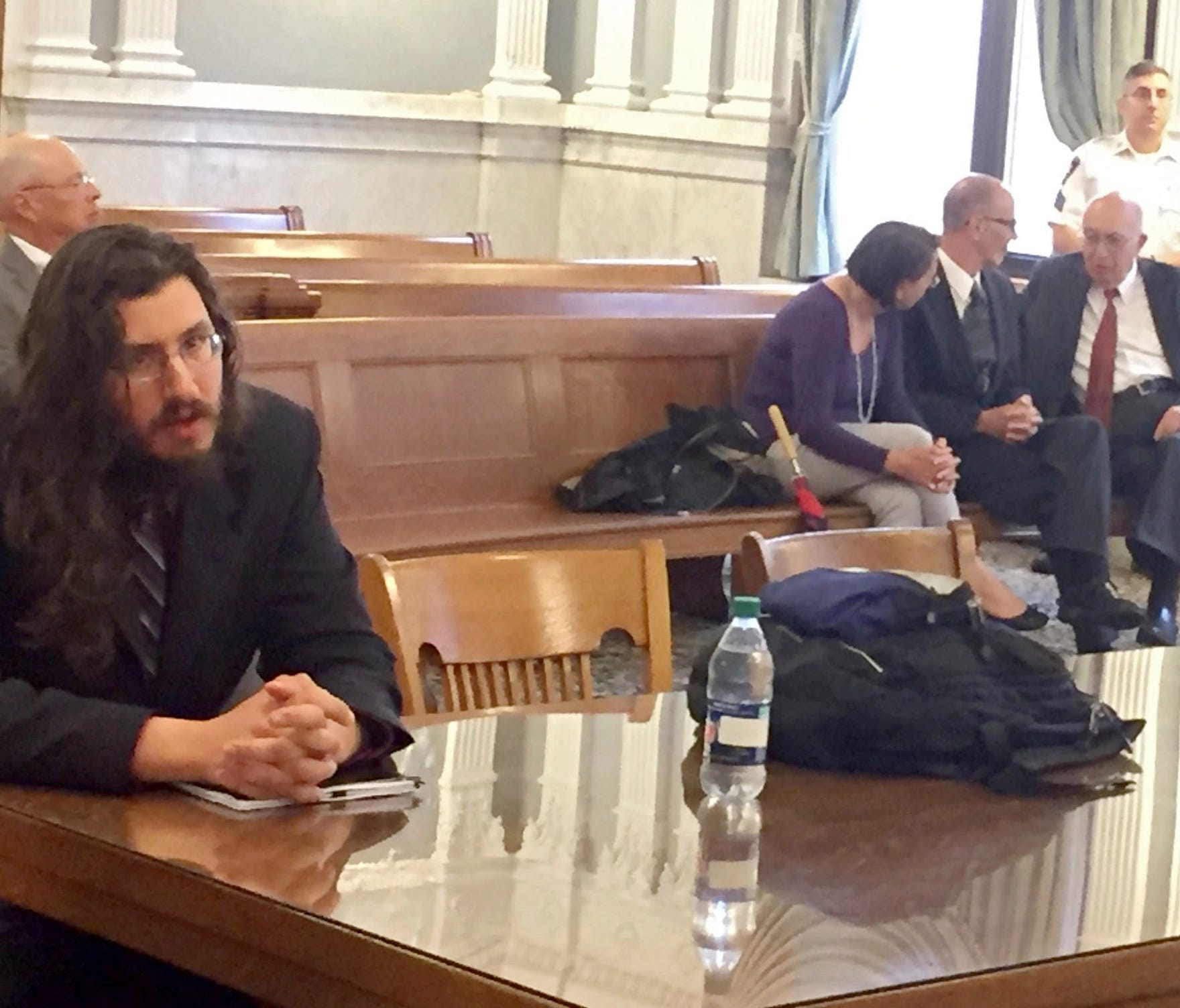 Michael Rotondo, left, sits during an eviction proceeding in Syracuse, N.Y., brought by his parents, Mark and Christina, of Camillus. The two parents confer with their lawyer, Anthony Adorante, in the court gallery behind. Rotondo told the judge Tues