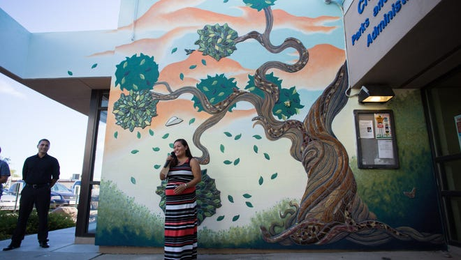 "Margarita Paz-Pedro, lead artist of ""When Trees Play"" is pictured speaking during the mural's ceremony at ""Mondy"" Castaneda Service Center in downtown Las Cruces Thursday."