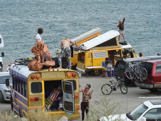 A woman dances on top of a van while others set up camp on Blockhouse Beach at Pyramid Lake Monday.