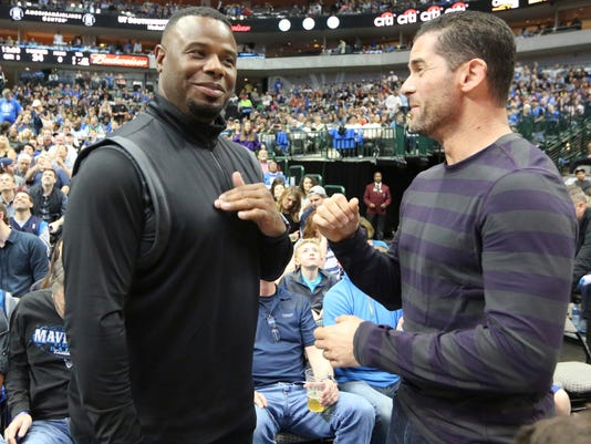 Former Major League Baseball players Ken Griffey Jr., left, and Michael Young visit  during the first half of an NBA basketball game between the Minnesota Timberwolves and Dallas Mavericks on Sunday, Feb. 28, 2016, in Dallas. (AP Photo/LM Otero)