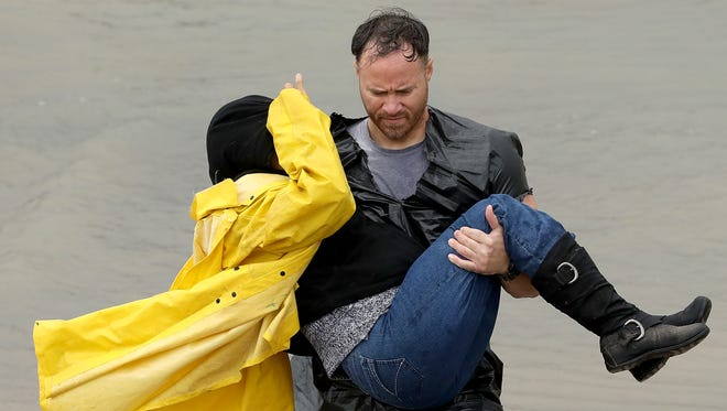 A volunteer carries a woman whose home was impacted by severe flooding following Hurricane Harvey in north Houston Aug. 29, 2017, in Houston, Texas.