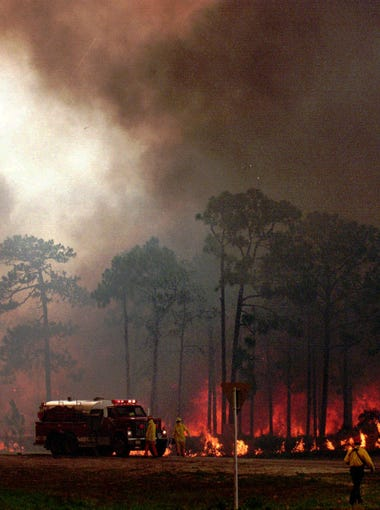 Dense smoke and fire engulf Route 1 in Scottsmoor in Brevard County on July 1, 1998. The fire on the west side of the road jumped to the east side and firefighters were trying to contain it.