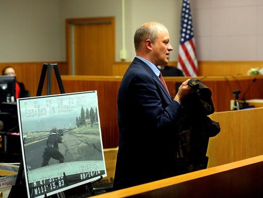Cascade County Attorney John Parker holds up Deputy