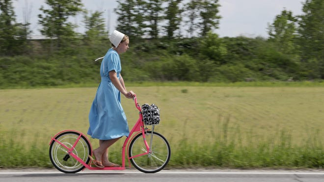 An Amish girl rides her scooter, Wednesday, May 27, 2020, near Middlefield in northeast Ohio.