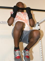 Amontai Meadows, 7, of Middletown, does pull-ups at