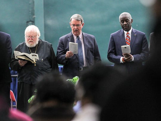 """Father David Randolph, left, the Rev. Jim Thomason, middle, and Anderson Mayor Terence Roberts sing """"Lift Every Voice and Sing"""" at a birthday celebration Monday for the Rev. Martin Luther King Jr. at the Civic Center of Anderson."""