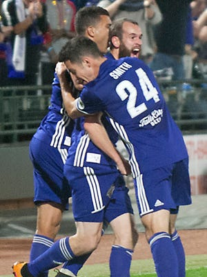 Louisville City FC defender Tarek Morad, top left, and Louisville City FC defender Kyle Smith, right, sandwich Louisville City FC midfielder Brian Ownby, top right, after Ownby scores the first goal of the game.04 November 2017