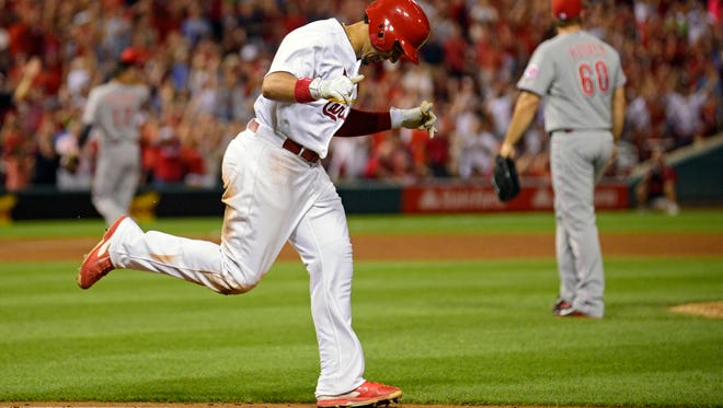 Cardinals center fielder Jon Jay celebrates after being hit by a pitch from Reds relief pitcher J.J. Hoover at the end of Tuesday's game.