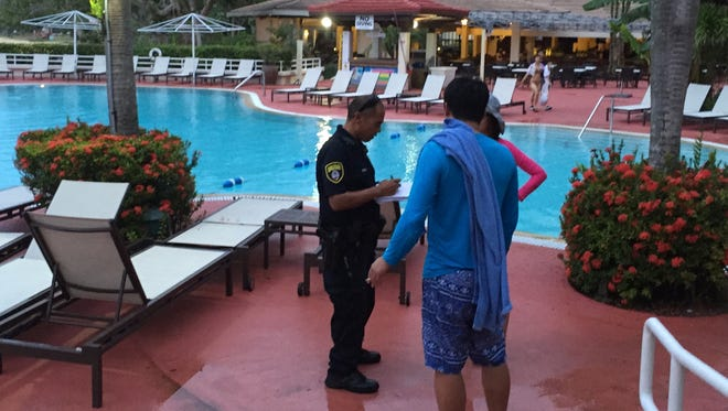A Guam Police Department officer takes a statement from witnesses at the Guam Hilton Resort and Spa on July 4, shortly after a 5-year-old girl nearly drowned in the hotel's swimming pool. The girl was taken to Guam Memorial Hospital where she was said to be in stable condition.