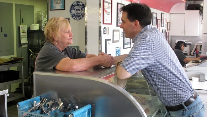 Republican presidential candidate Wisconsin Gov. Scott Walker talks with Wilma Wagner, a worker at Penny's Diner, during a campaign stop on Wednesday, Aug. 26, 2015, in Missouri Valley, Iowa.