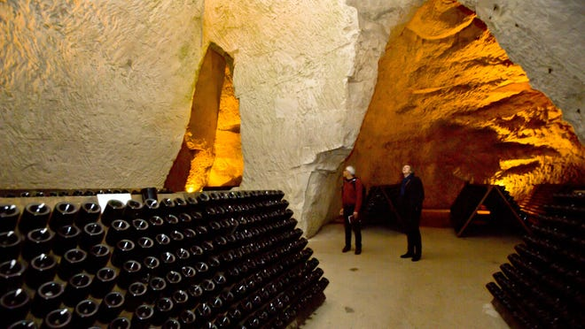 Visitors stand near bottles of Champagne in the caves of the Taittinger Champagne House in Reims, France.