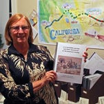 Mary Randall shows the cover of her latest teacher's guide to Salinas' past. A Westward Movement game board is posted on the wall behind her.