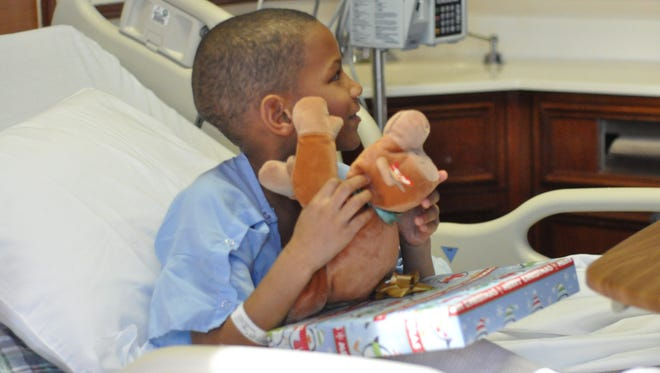 Marcus Simon, 7, was among the pediatric patients at Rapides Women's and Children's Hospital who got an early Christmas present from hospital volunteers and the Chick-fil-A cow on Friday.