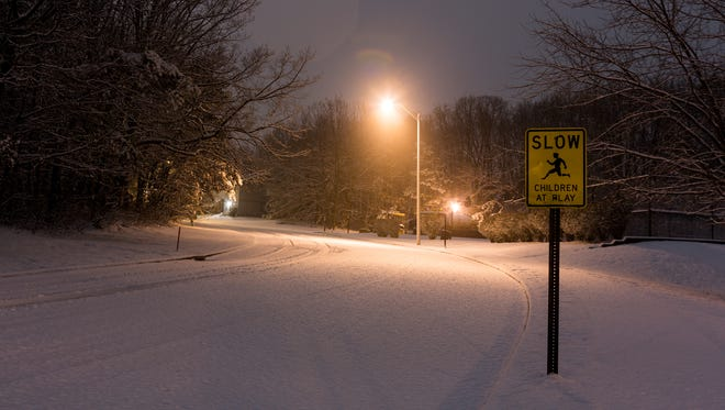 Children at play in Howell, NJ at 1:30am while snow flakes hit the ground.