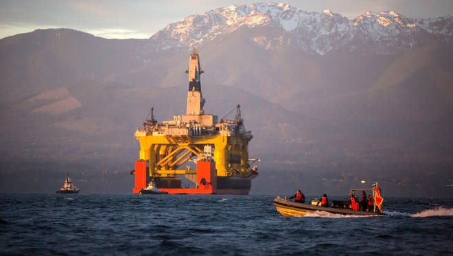 With the Olympic Mountains in the background, a small boat on April 17, 2015,  crosses in front of an oil drilling rig as it arrives in Port Angeles, Wash., aboard a transport ship after traveling across the Pacific. Royal Dutch Shell hopes to use the rig for exploratory drilling during the summer open-water season in the Chukchi Sea off Alaska's northwest coast, if it can get the permits.