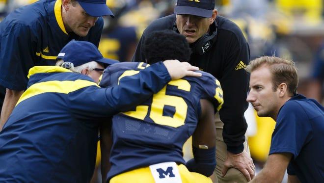 Michigan coach Jim Harbaugh, center, checks on cornerback Jourdan Lewis against Oregon State at Michigan Stadium.
