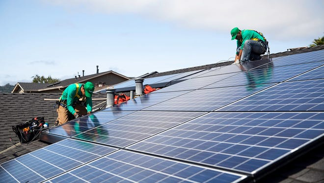 Workers install photovoltaic cells on a roof for SolarCity